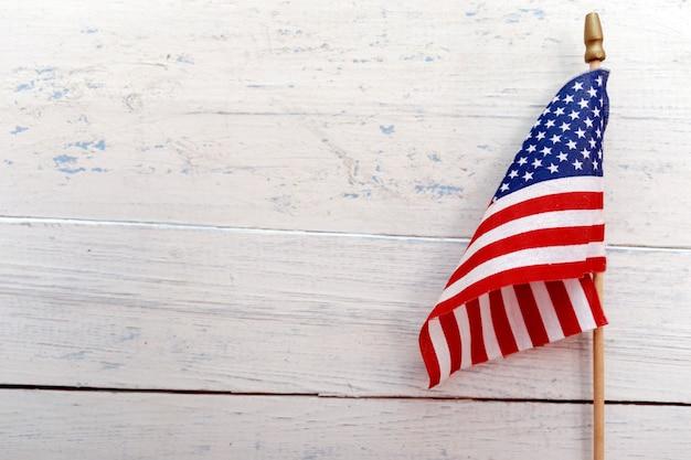 コピースペースを持つ素朴な木製の背景に掛かっているアメリカ合衆国の国旗