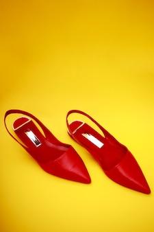 赤の女性靴は黄色に分離されました。