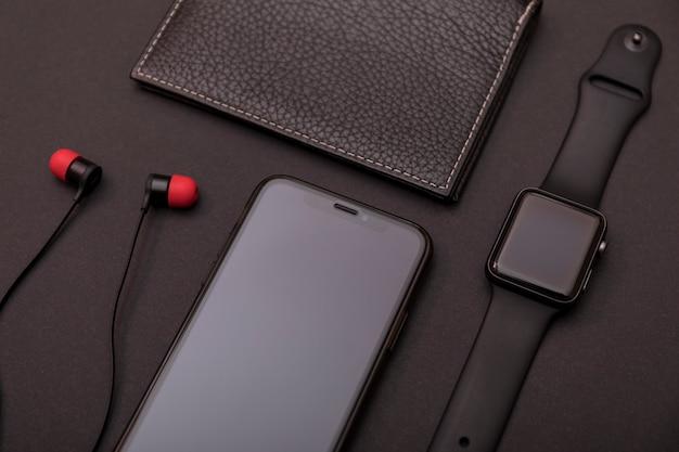 黒革の財布、スマートウォッチ、スマートフォン、イヤホンのセット。