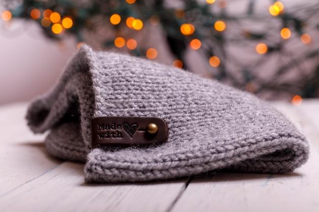 Зимняя вязаная шапка белый деревенский деревянный столик. рождество и новый год фон.