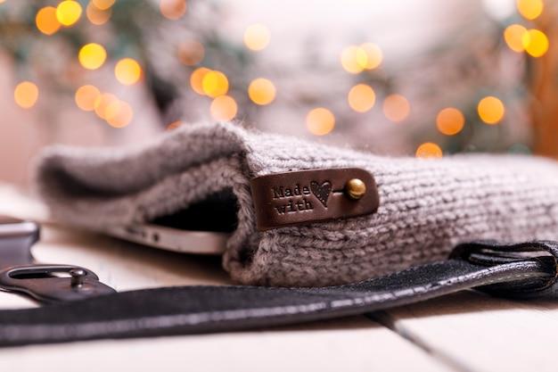 Зимняя квартира лежала с умными часами, таблеткой, вязаной шляпой и поясом на белом простоватом деревянном столе. рождество и новый год фон.