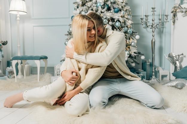 Счастливая пара, муж и жена сидят возле украшенной елки в канун рождества. новогодние и рождественские праздники