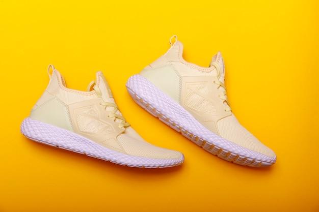 Спортивная обувь тема в желтом цвете. пара желтых кроссовок на желтом фоне. модный летний цвет.