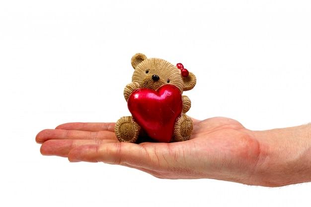 Мужской рукой, держащей фигурка мишка изолированы. минималистичная концепция.