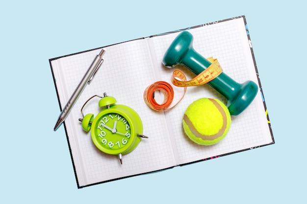 テキスト、フィットネス、スポーツの空の空白の健康的なライフスタイルのコンセプト。ダンベル、アラール時計、分離された水のボトルとテニスボール