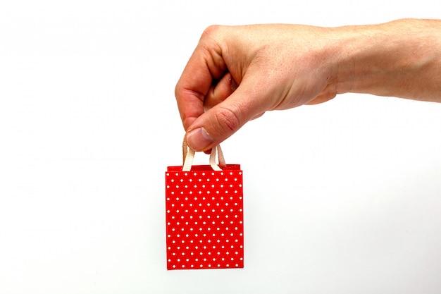 Мужская рука держа красную сумку подарка изолированный. минималистичная концепция.