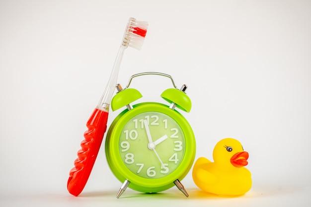 Фото зеленого будильника и зубной щетки. время чистить зубы. стоматологическая помощь, концепция личной гигиены фото. важное напоминание детям и взрослым заботиться о своих зубах.