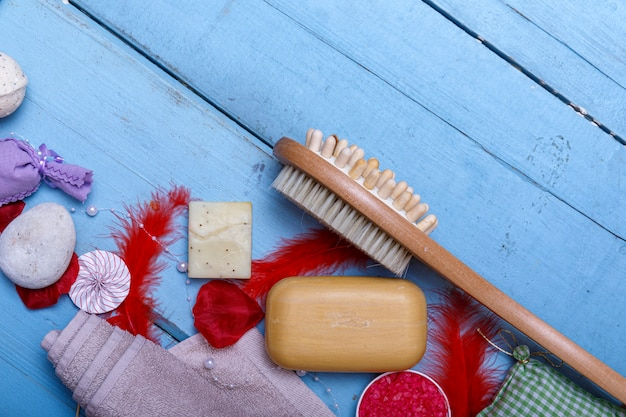 スパキットまたは青い木製のテーブルに自然なオーガニック製品のコンセプトを設定します。石鹸と液体。アロマテラピーピンクソルト。コピースペースの平面図です。