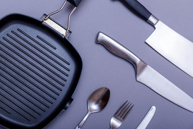 Металлические ножи с черным на сером столе, противень для гриля, полотенце. плоская планировка, макет.