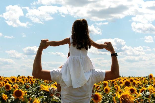 Отец и маленькая дочь в поле на заходе солнца. счастливая семья, отец и дочь весело проводят время в парке.