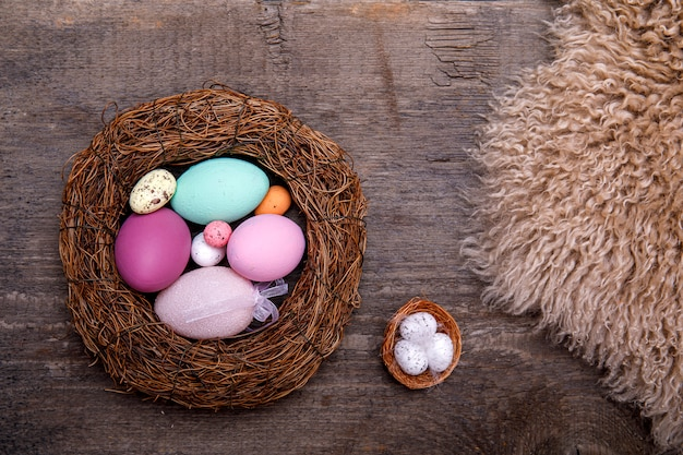 Красочные пасхальные яйца в гнезде на деревенской деревянной предпосылке с космосом экземпляра для текста. пасха минимальная концепция с поверхностью.