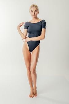 若いセクシーなブロンドの女性が黒のおしゃれな水着でポーズします。理想的な体の女の子。スタジオ撮影。