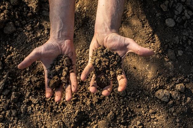 Почва, культивируемая грязь, земля, земля, коричневая предпосылка земли. органическое садоводство, сельское хозяйство. природа крупным планом. экологическая текстура, рисунок. грязь на поле.