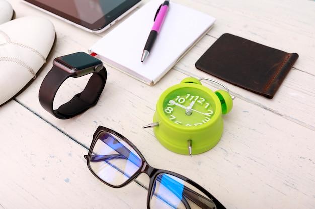 Блокнот с ручкой, умные часы и телефон, кроссовки на потертой белой древесине