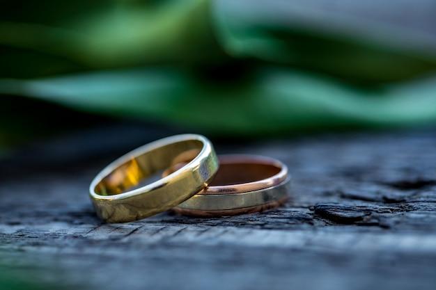 美しい葉の枝とヴィンテージの木製のテクスチャ背景の結婚指輪。