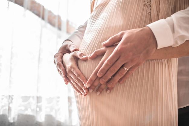 妊娠中の女性と彼女の夫が赤ちゃんのバンプにハートの形で手を握っています。おなかにハートの形を作るカップルのクローズアップ。赤ちゃんを期待して愛する将来のカップル。家族の概念。