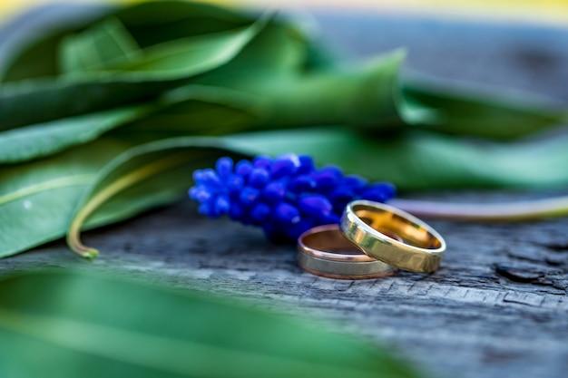 Взгляд конца-вверх золотых обручальных колец и красивых маленьких голубых цветков на деревянной столешнице