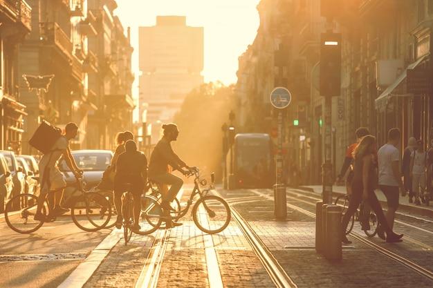 Уличная фотография, люди, пересекающие дорогу во время заката в городе бордо, франция. винтажный стиль