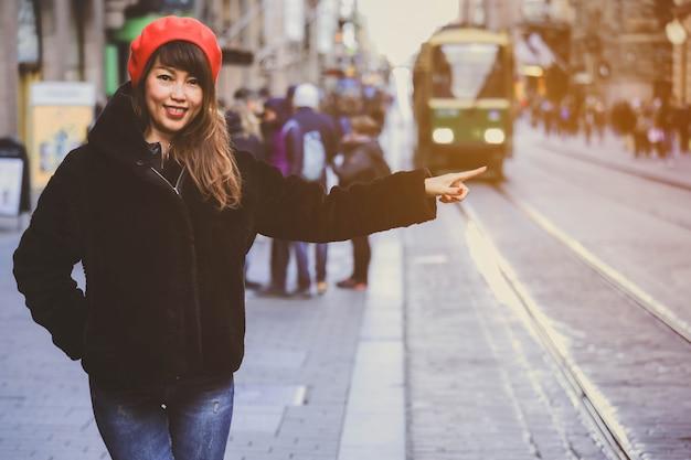 Азиатка звонит одному из старых трамваев в центре хельсинки, финляндия