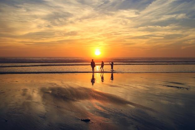 Люди любят гулять по пляжу во время красочного заката с его отражением