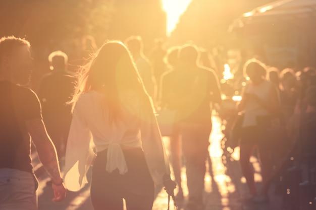 太陽フレアが付いている通りを歩いて背景をぼかした写真人