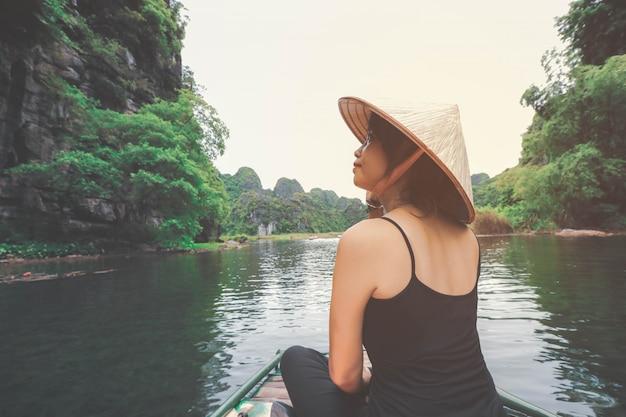 ニンビン省、ベトナムでの休暇中に木製のボートに座っているアジアの女性