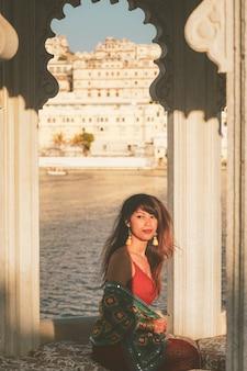 背面には、ウダイプル、インドの都市宮殿博物館とアーチの窓の開口部に座っているアジアの女性