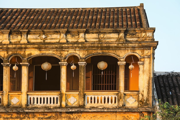 ホイアンの古い家々窓にぶら下がっている提灯のある古代の町