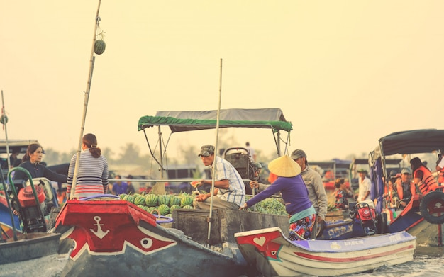 Вьетнамские торговцы покупают арбуз на плавучем рынке нга нам