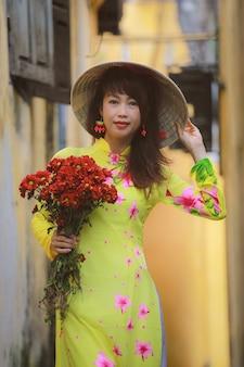 古代都市ホイアンを歩いてアオダイベトナムの伝統的な衣装で美しい女性