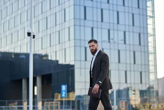 Человек в костюме, стоя в передней небоскребов, вызов с ним работать в офисе. молодой предприниматель кавказской.