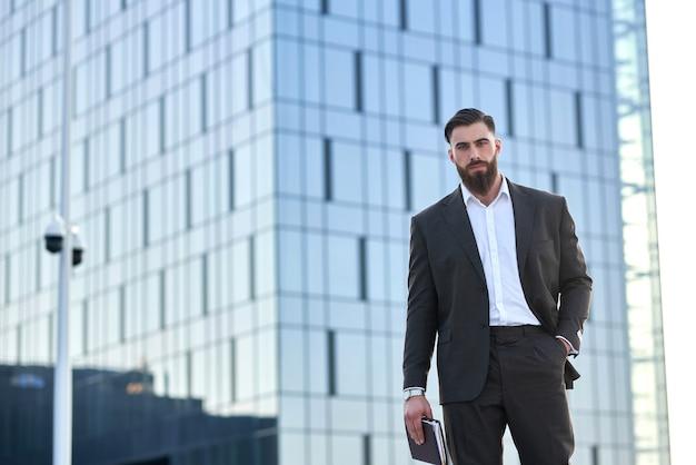 Успешный бизнесмен в костюме перед гигантским современным бизнес-центром