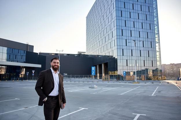 Портрет бизнесмена перед корпоративными зданиями