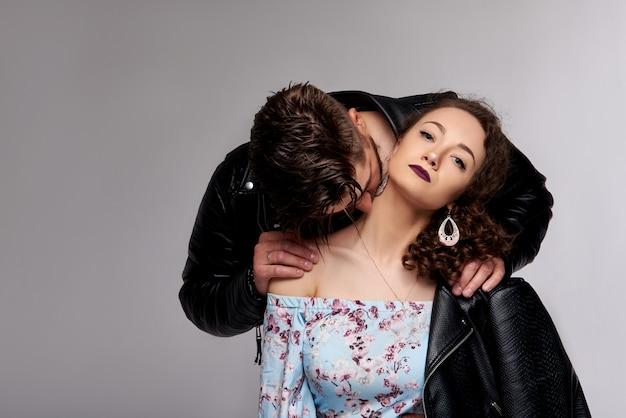 Фото красивой пары в кожаных куртках. повседневные наряды. мужская и женская коллекция. серая стена.