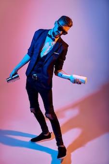 Бармен человек жонглирование бутылками и тряску, на розовый, синие неоновые огни.