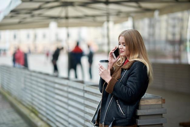 Привлекательная молодая девушка. говорить по мобильному телефону в парке. привлекательная молодая леди разговаривает со своими друзьями по мобильному телефону и пьет кофе