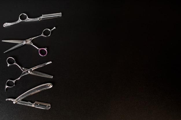 Оборудование парикмахерской на черной предпосылке с местом для текста. профессиональные парикмахерские инструменты. расческа, ножницы