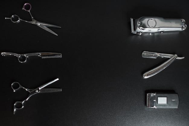 Оборудование парикмахерской на черной предпосылке с местом для текста. профессиональные парикмахерские инструменты. гребень, ножницы, машинки для стрижки волос и машинка для стрижки волос изолированы
