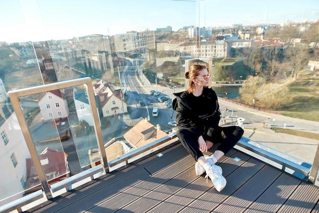 ガラスのフェンスとガラスに立っている女の子はピンクのサングラスで街を見ています。