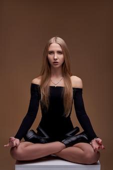 白い白人の女の子の肖像画。美しいスポーツボディを持つ若いモデル。茶色の壁にビキニのブロンド。