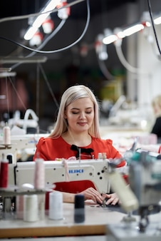 Красивая девушка в красном платье в пошиве одежды. эксклюзивный пошив платьев на заказ. девушка шьет платье на швейной машинке. европейская женщина работает в швейной мастерской.