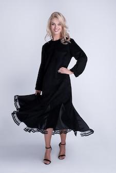 トレンディなドレス、メイクのファッションの若い女性。スタイリッシュなウェーブのかかった髪型、黒い服。灰色の化粧ポーズ