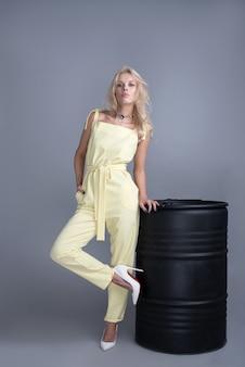 トレンディなドレス、メイクのファッションの若い女性。スタイリッシュなウェーブのかかった髪型、黄色の服。灰色の背景に黒い樽に近いポーズ化粧