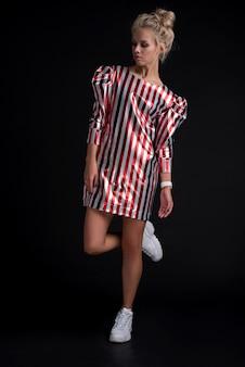 Портрет очаровательной женщины в полосатом платье. изолированный черный фон