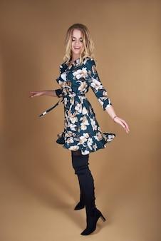 花春夏ドレスの金髪の若い女性。茶色の壁でポーズの女の子。夏の花の服。スタイリッシュなウェーブのかかった髪型。ファッション写真。