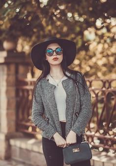 Симпатичная брюнетка с красными губами в шляпе и очках позирует в городе