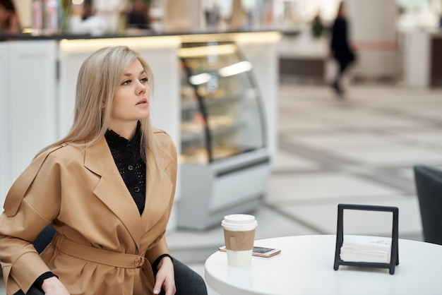 Молодая женщина сидит в кафе торгового центра, болтает по мобильному телефону и держит в руке бумажный стаканчик кофе.