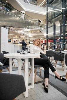 Довольно молодая красивая блондинка с длинными волосами, сидя в кафе в торговом центре. привлекательная современная девушка в модной одежде наслаждается горячим напитком в помещении.