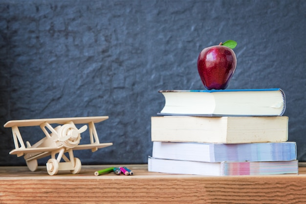 背景として黒と本で休んで赤いリンゴ、コンセプトメディア教育について考える