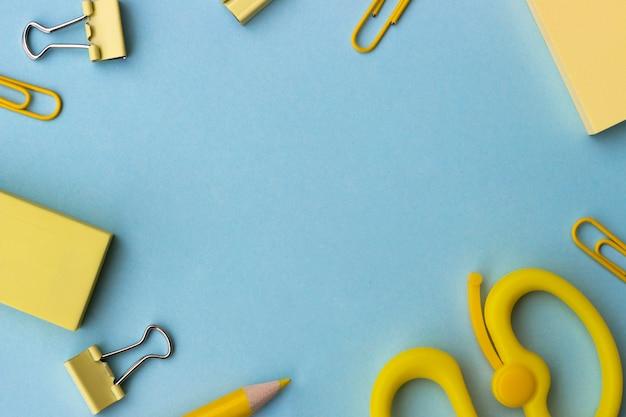 学校やオフィススタイルのコンセプトに戻る、青い背景に黄色の学用品とフレーム